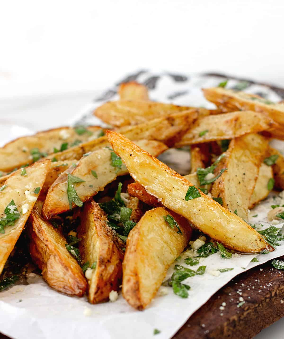 Mound of potato wedges with parsley on white paper