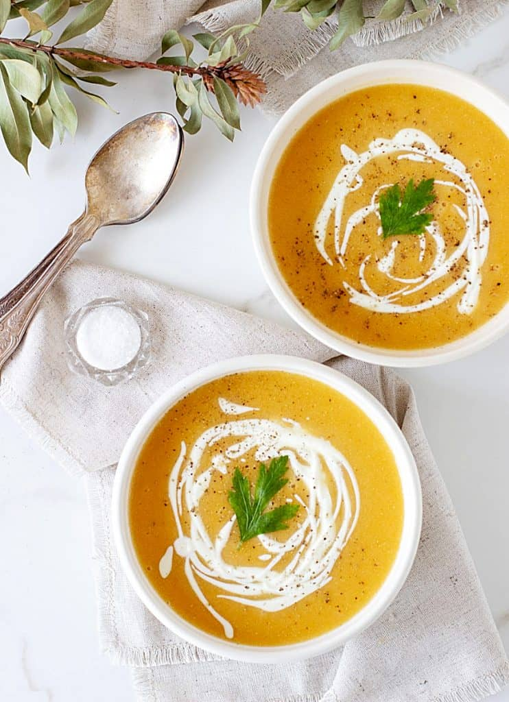 Two white bowls with pumpkin soup, spoons, salt, white background