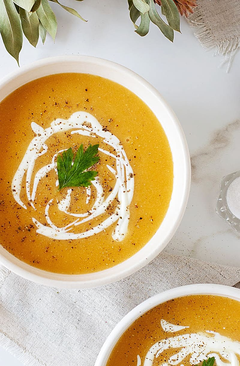 White bowl with pumpkin soup, cream drizzle, on a marble background