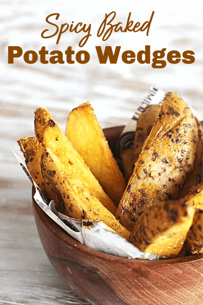 Baked potato wedges in wooden bowl on white surface, image with text