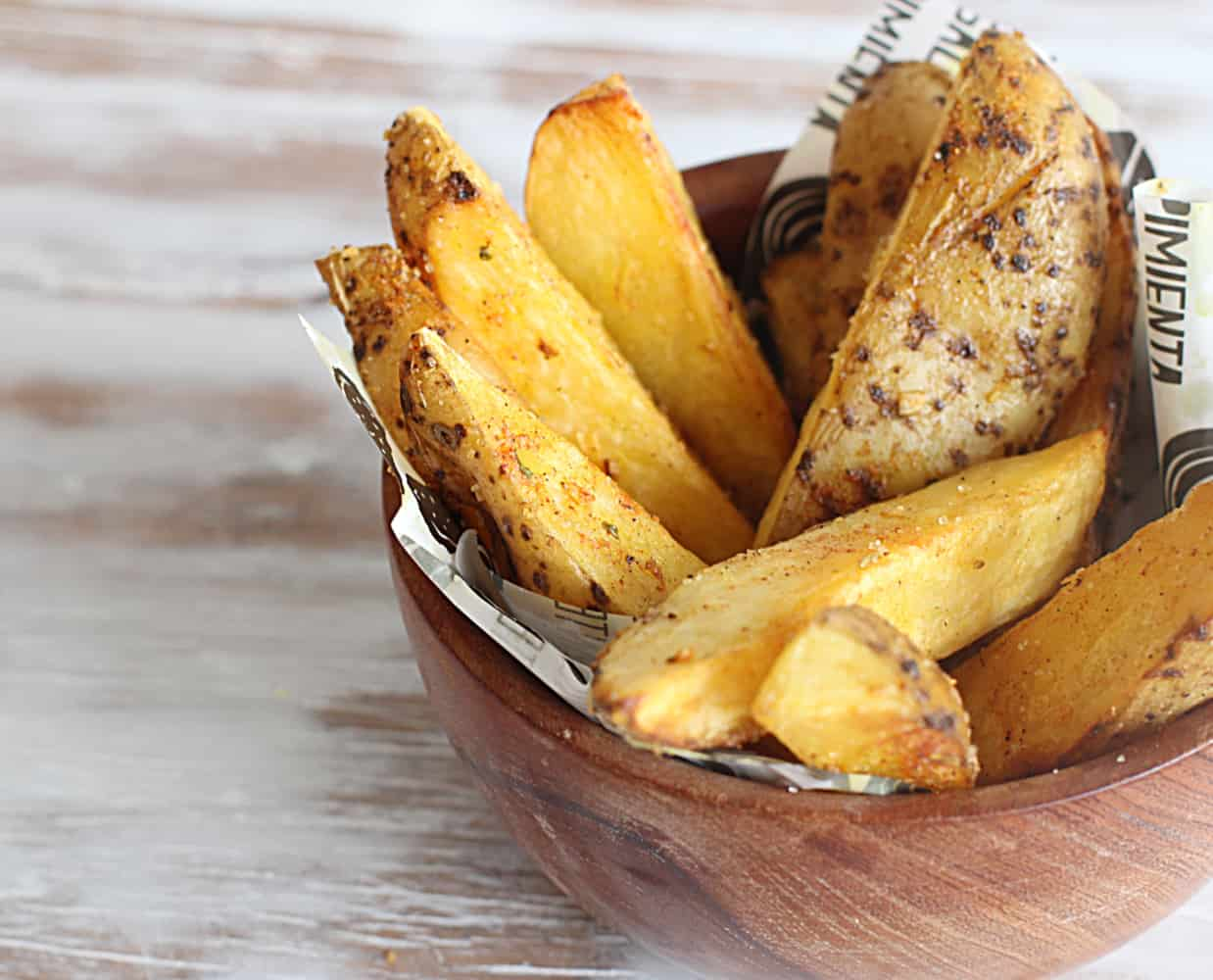Small wooden bowl with skin-on potato wedges, a whitish surface