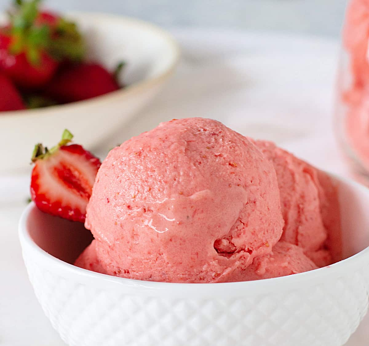 White patterned bowl with strawberry ice cream, more strawberries as background