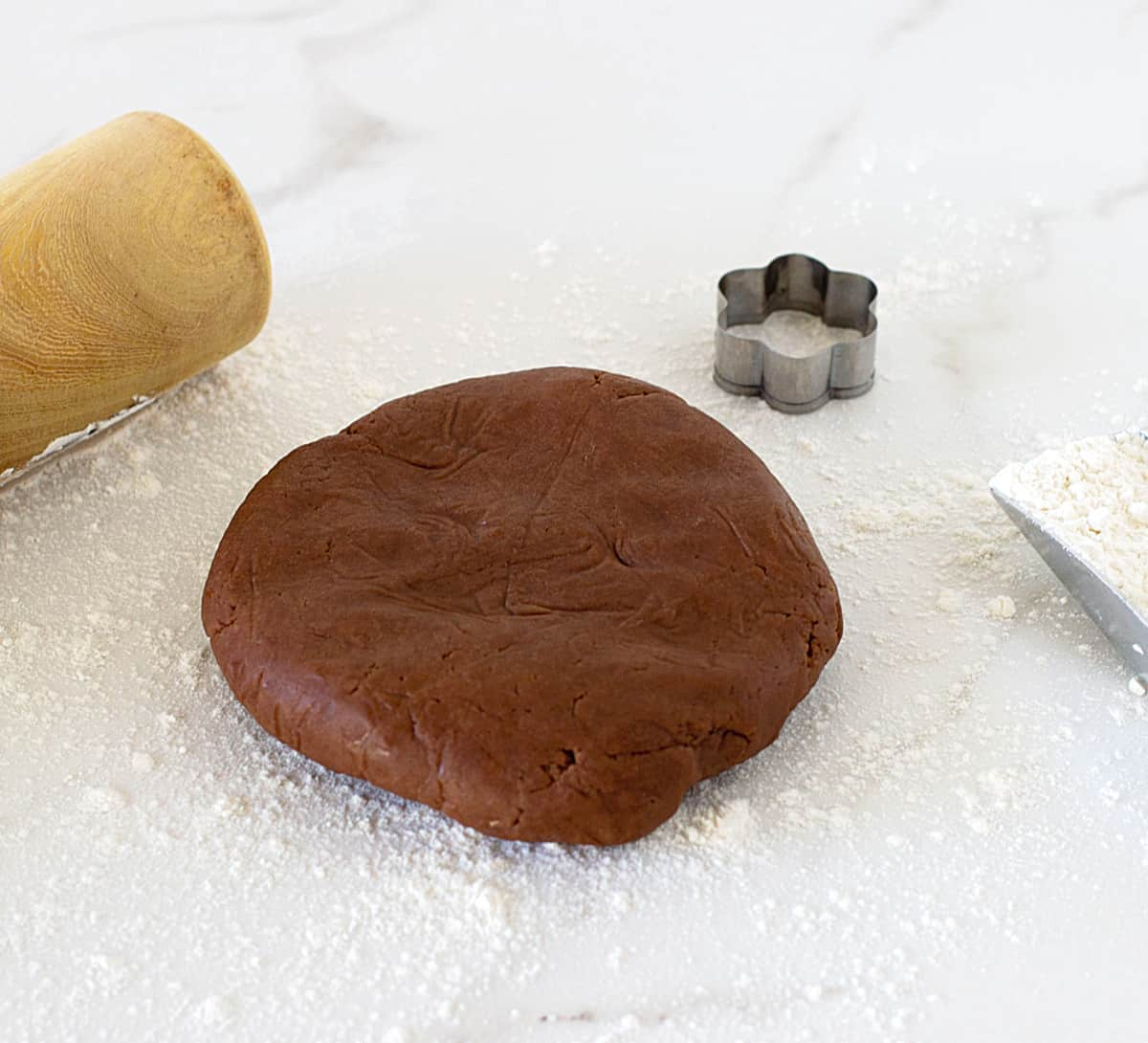 Chocolate pie dough round on white counter, flour and rolling pin