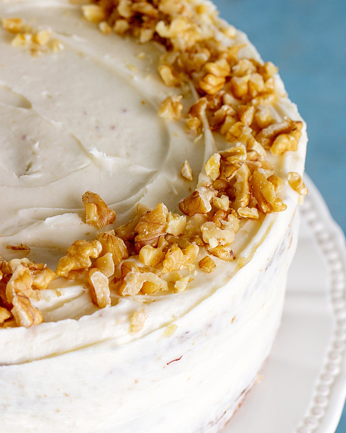 Partial top view of whole frosted cake on a white cake stand with walnuts on top