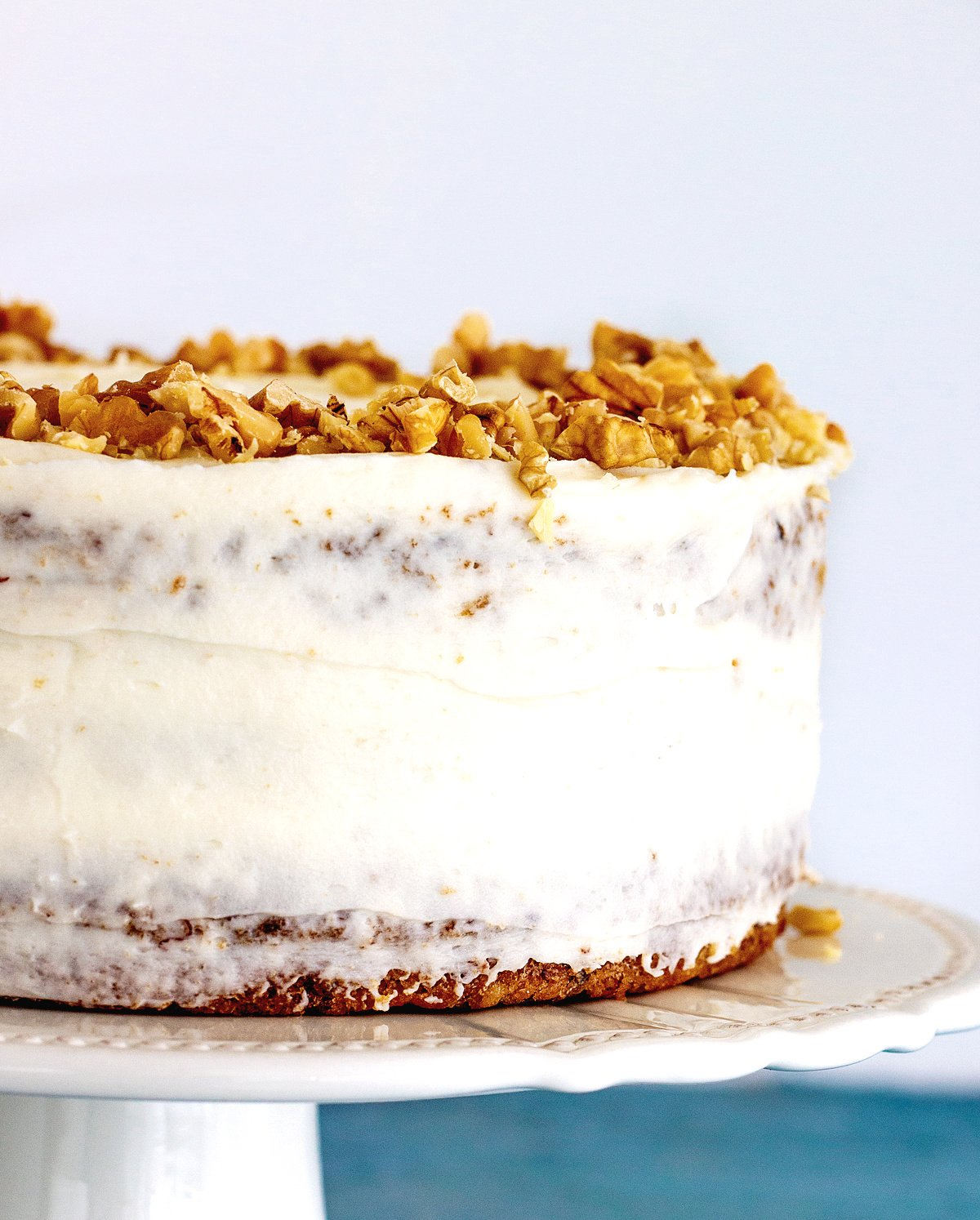 Partial view of whole frosted cake on a white cake stand with walnuts on top