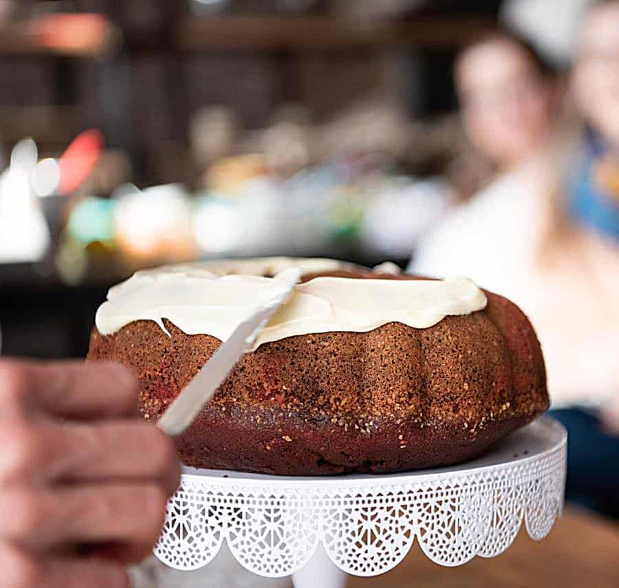 Hand frosting bundt cake on white cake stand