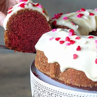 Hand lifting slice of red velvet bundt cake in white cake stand