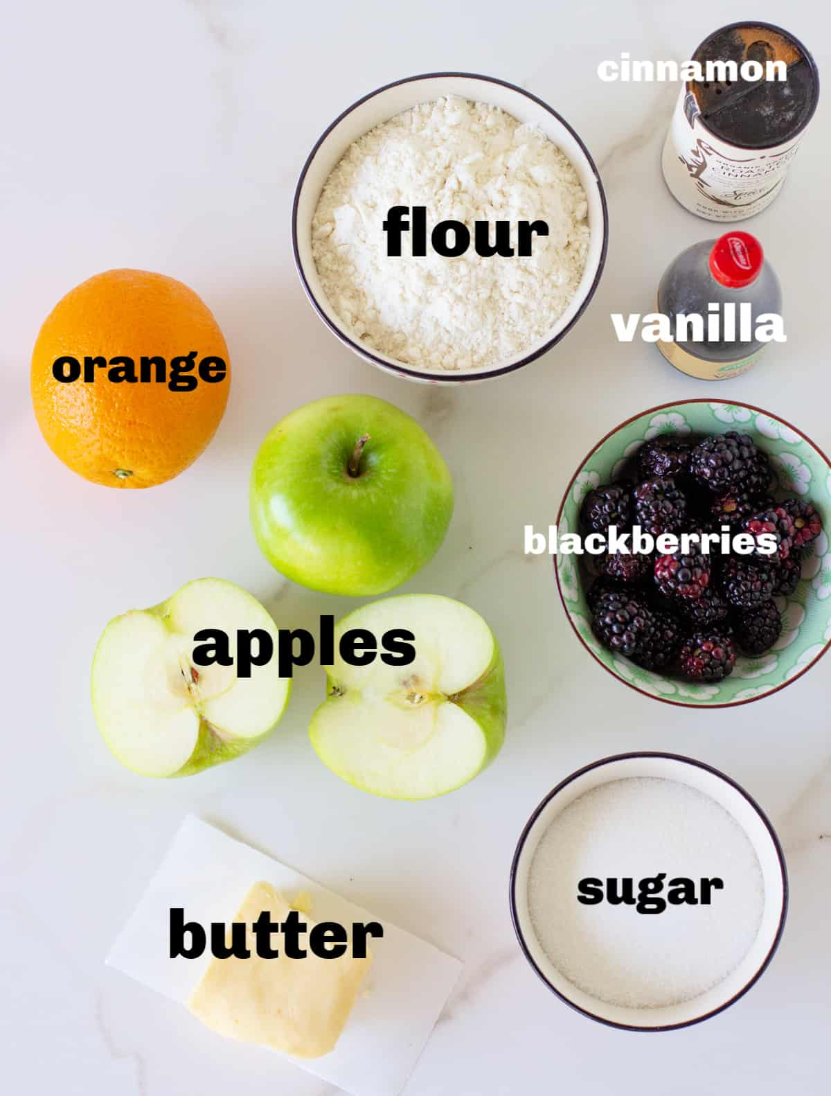 ingredients for apple blackberry crisp in bowls on white surface