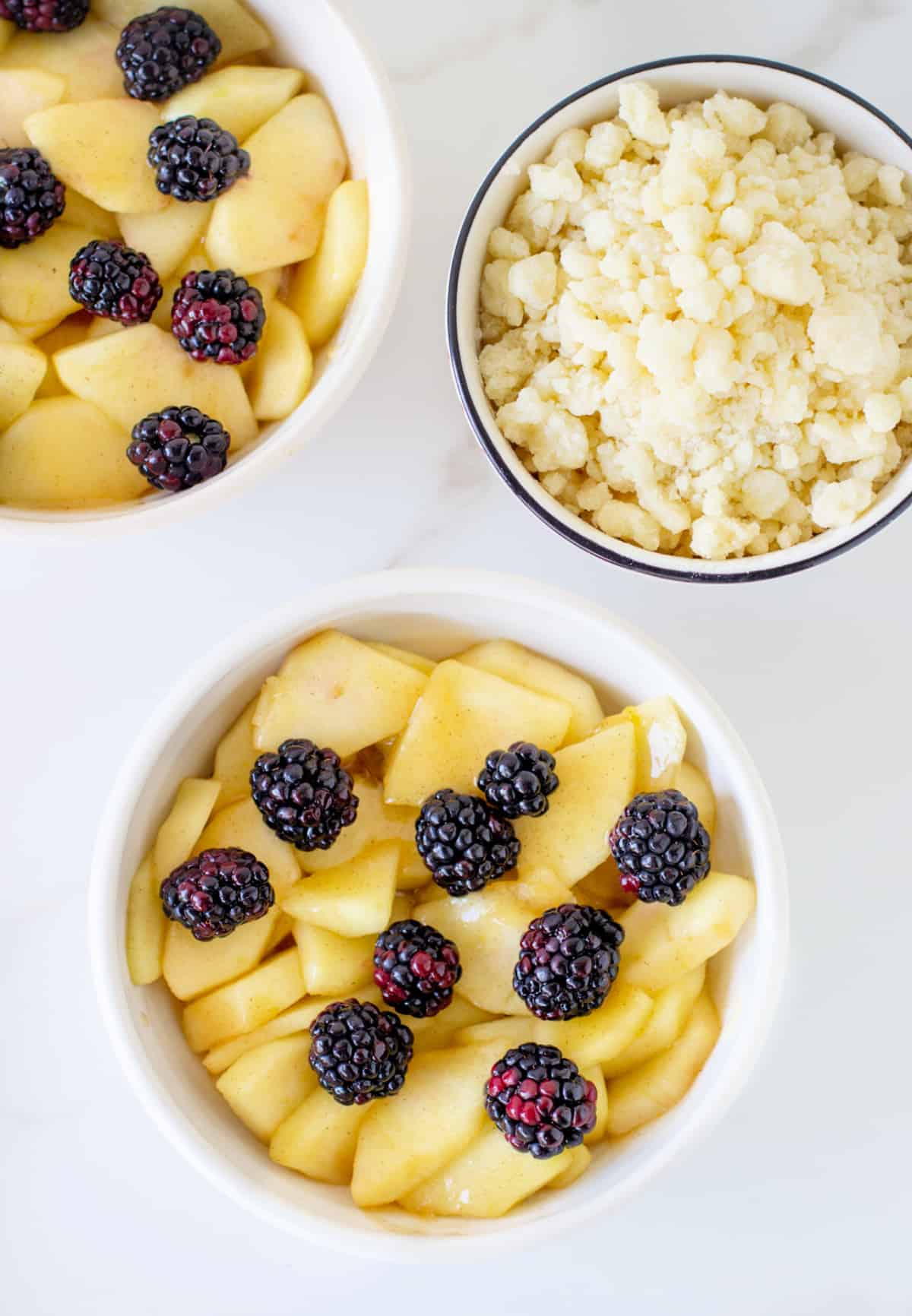White bowls with apples and blackberries, another with crumble; marble surface