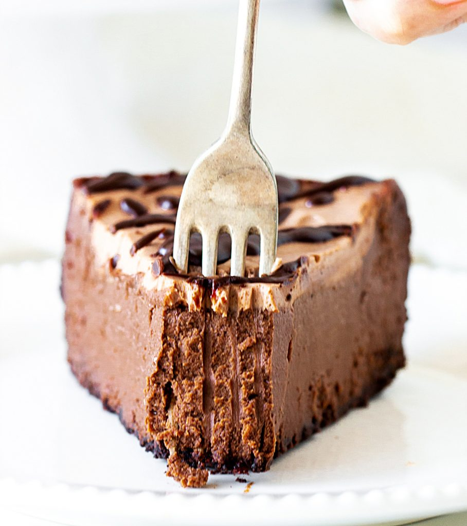 Sticking Silver fork into slice of chocolate cheesecake