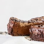 Pulling out slice of chocolate cheesecake with cake server