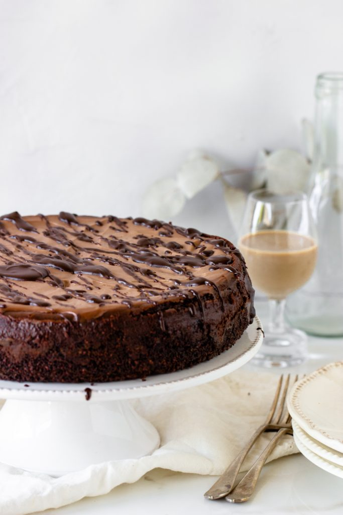 Whole chocolate cheesecake on white cake stand, glass with baileys, forks, piece of cloth