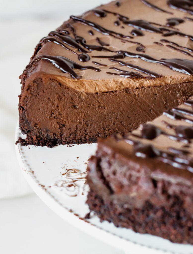Cut chocolate cheesecake on white plate