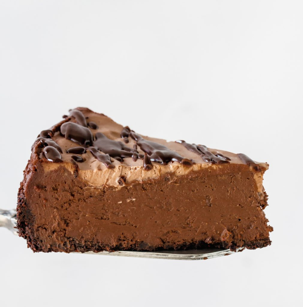 Slice of chocolate cheesecake on cake server, white background