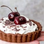 Hand holding small chocolate cream tart with whole cheeries on top