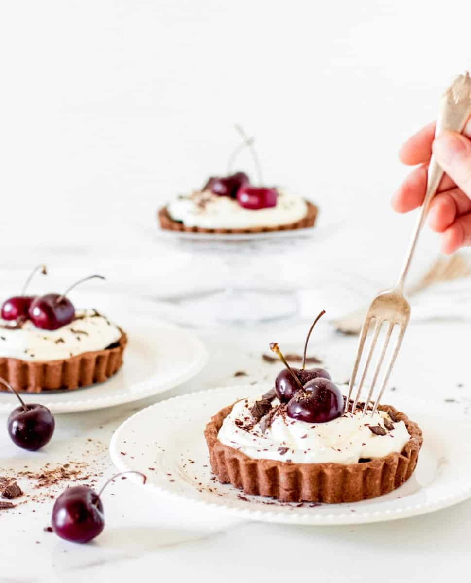 Several whole individual tarts with cherries and cream, hand holding silver fork