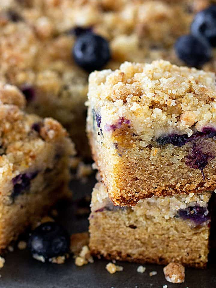 Squares of lemon cake with blueberries on metal surface, loose berries