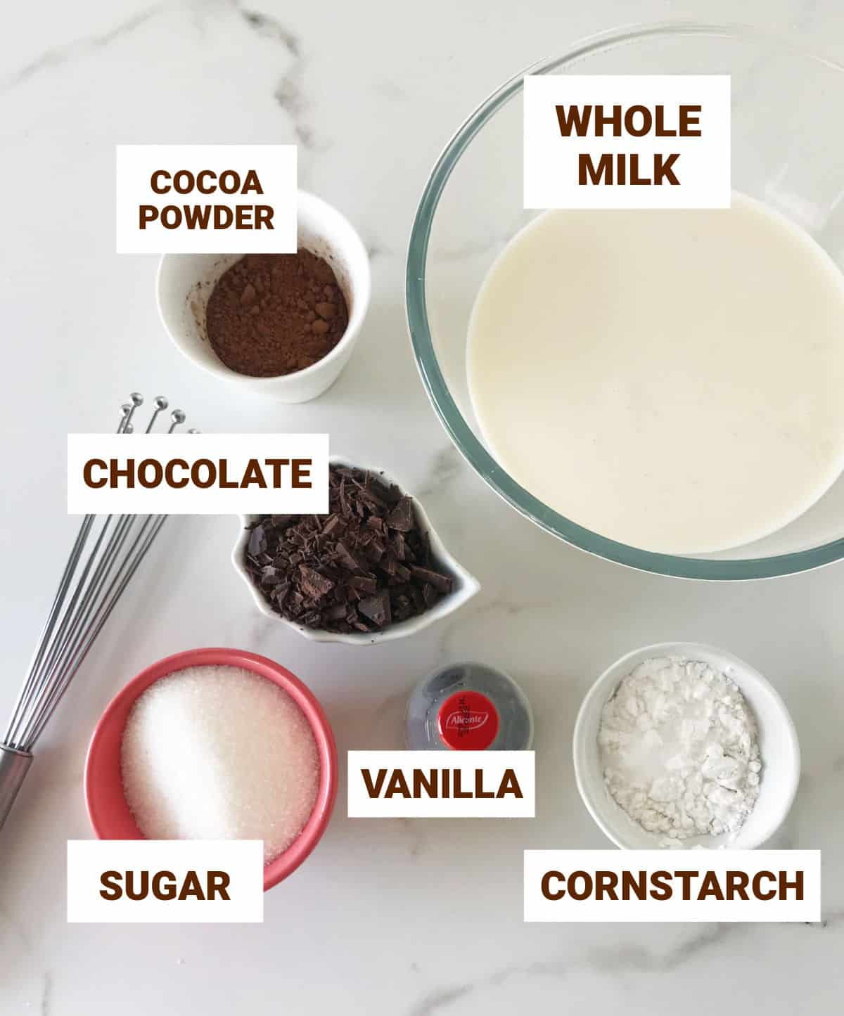 Chocolate pudding ingredients in bowls on white marble surface