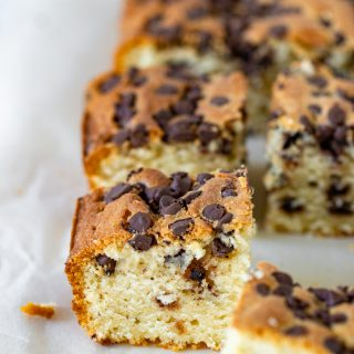 Squares of vanilla cake with chocolate chips on parchment paper