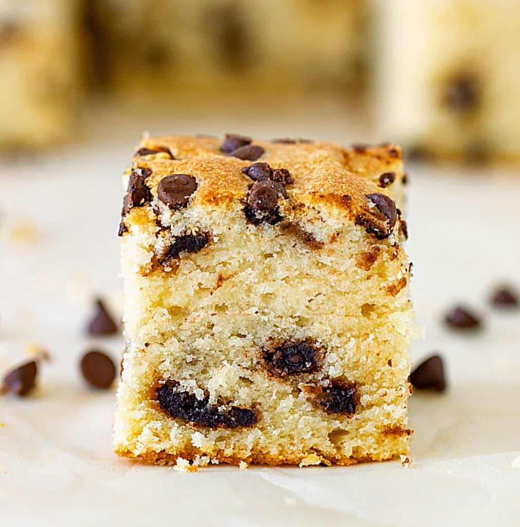 Square of vanilla cake with chocolate chips on white surface