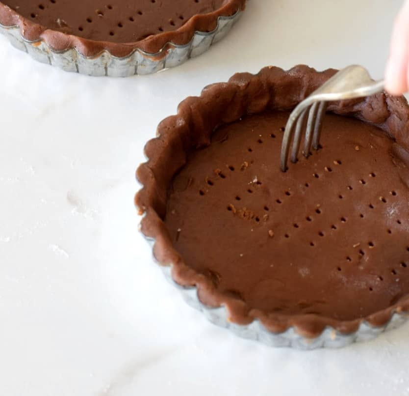 Pricking chocolate tart crusts with fork, white counter