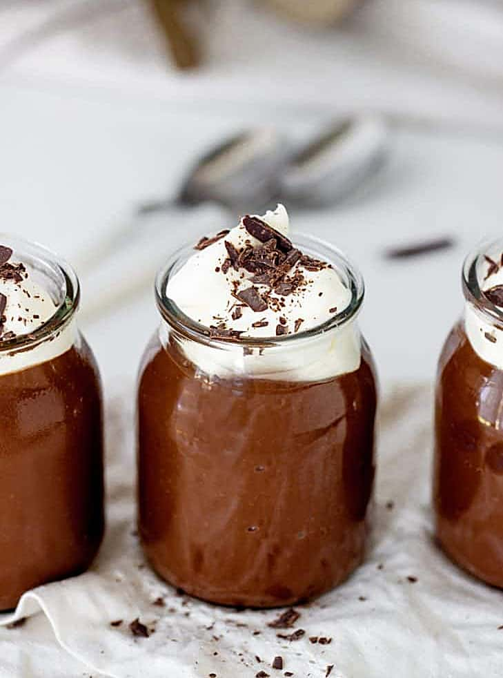 Glass jars with chocolate pudding and cream, grey background