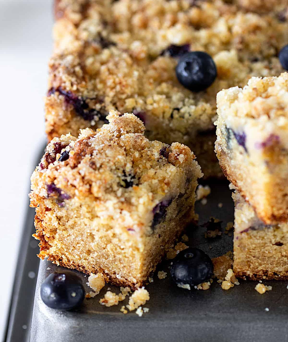 Close-up of crumb cake square on dark grey metal surface, loose blueberries around