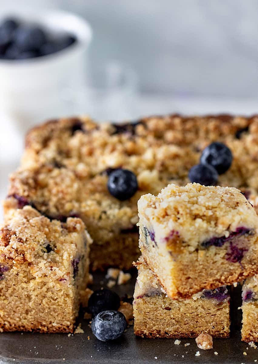 Half a crumb cake and squares with loose blueberries, grey background, bowl with blueberries