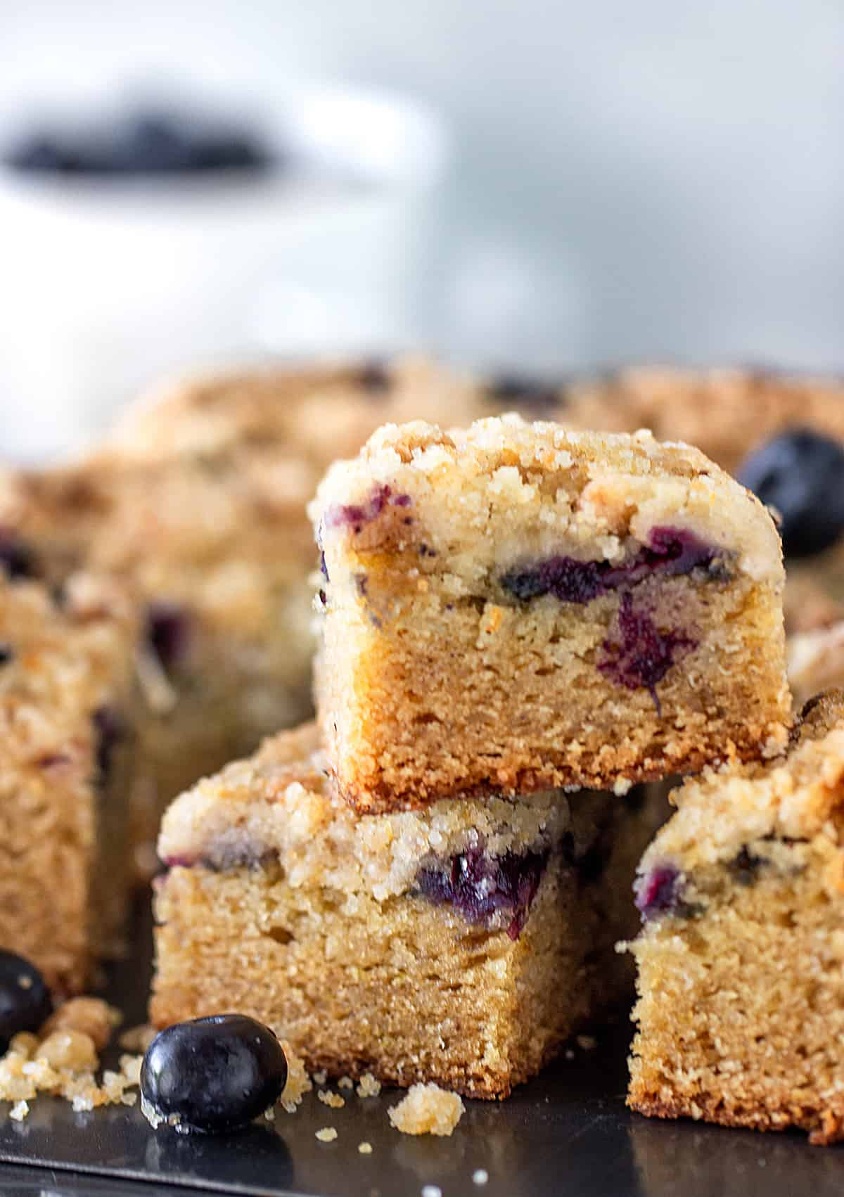 Crumb cake squares with blueberries on a metal surface