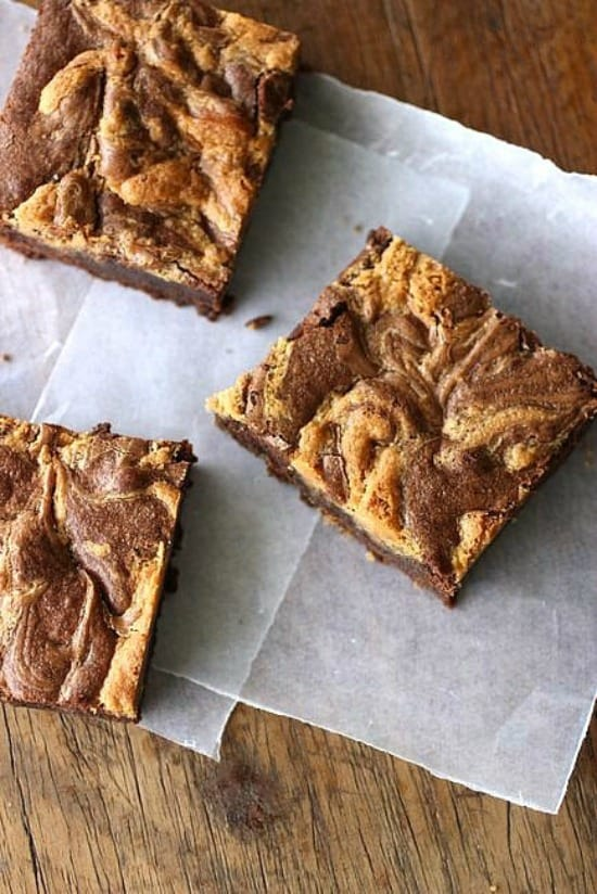 Squares of peanut butter brownies on parchment paper, wooden table