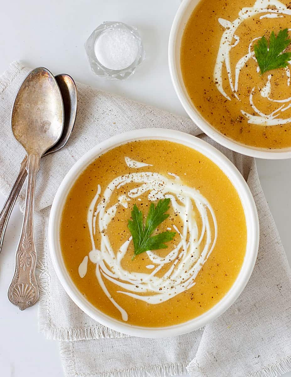 Close-up overview image of two white bowls with pumpkin soup, silver spoons, salt, beige background