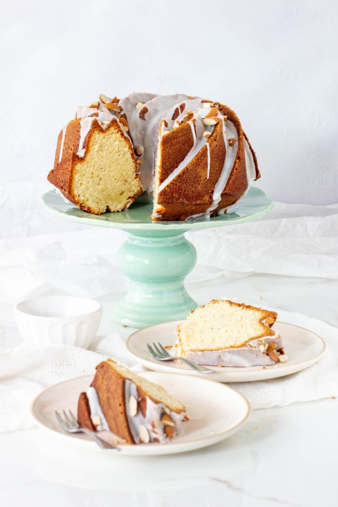 Green cake stand with glazed bundt cake, slices in plates