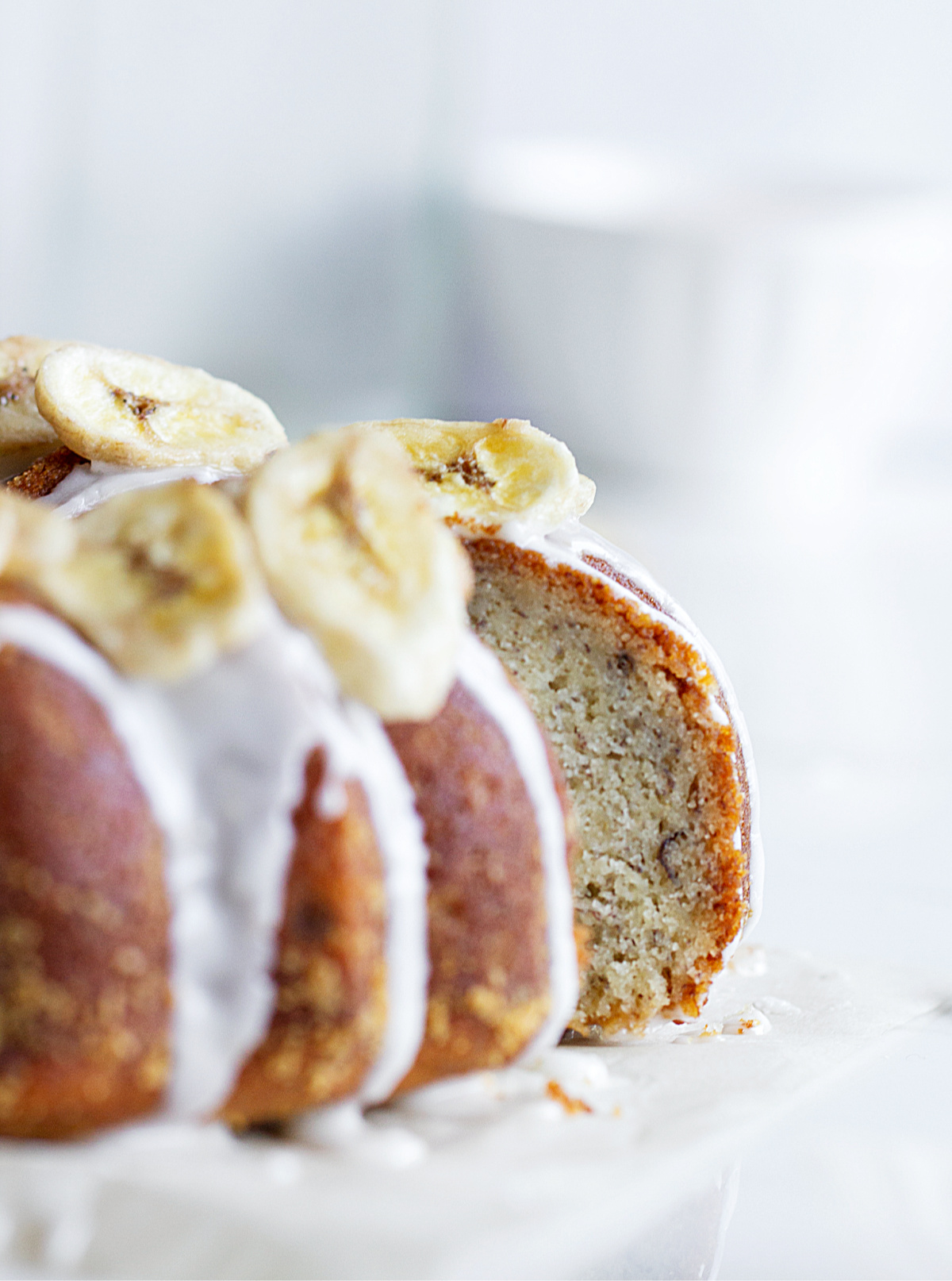 Focus on Slice of banana cake pulled out from whole bundt, blurred white background
