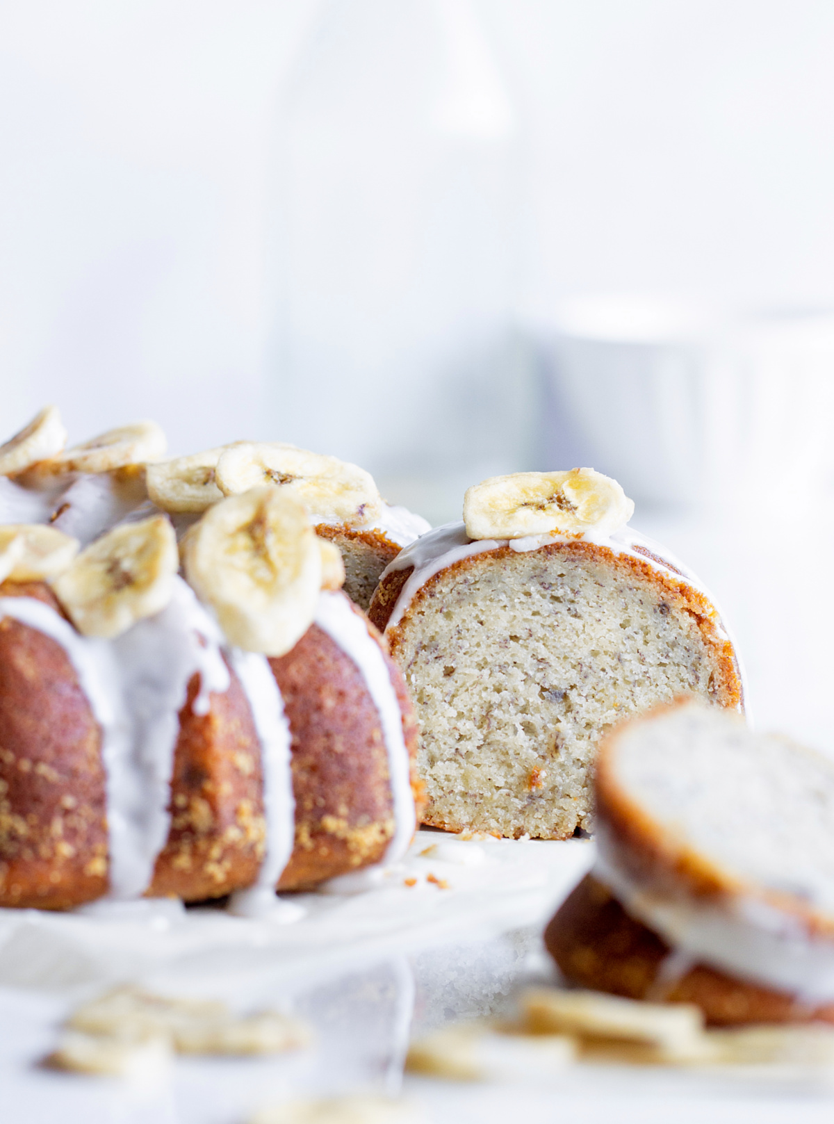 White background with focus on single banana bundt cake slice and blurred rest of cake