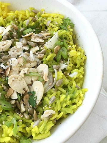 White bowl of green rice with almonds and seeds on white marble