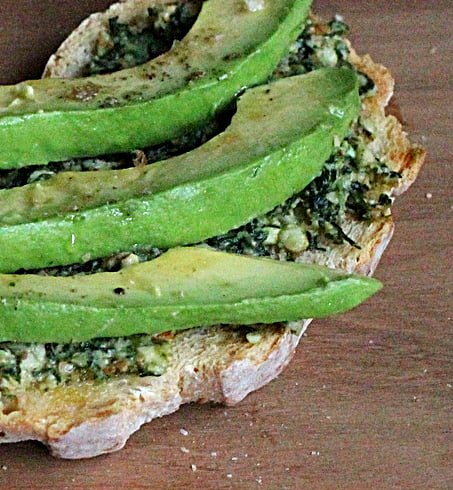 Piece of bread with pesto and slices of avocado on a wooden board