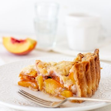 Slice of peach pie on white plate, silver fork, white background, peach wedge