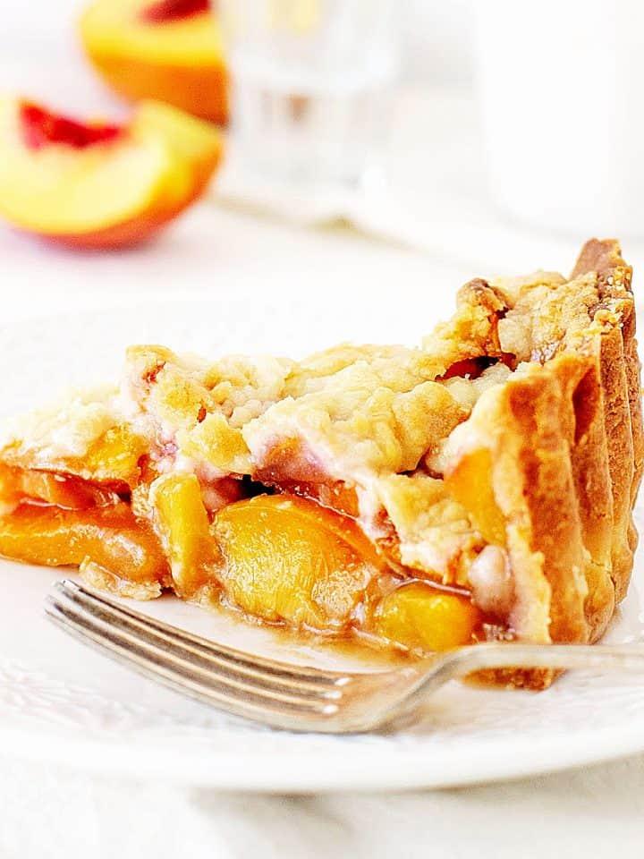 Slice of peach pie on white plate, white background, peach wedge