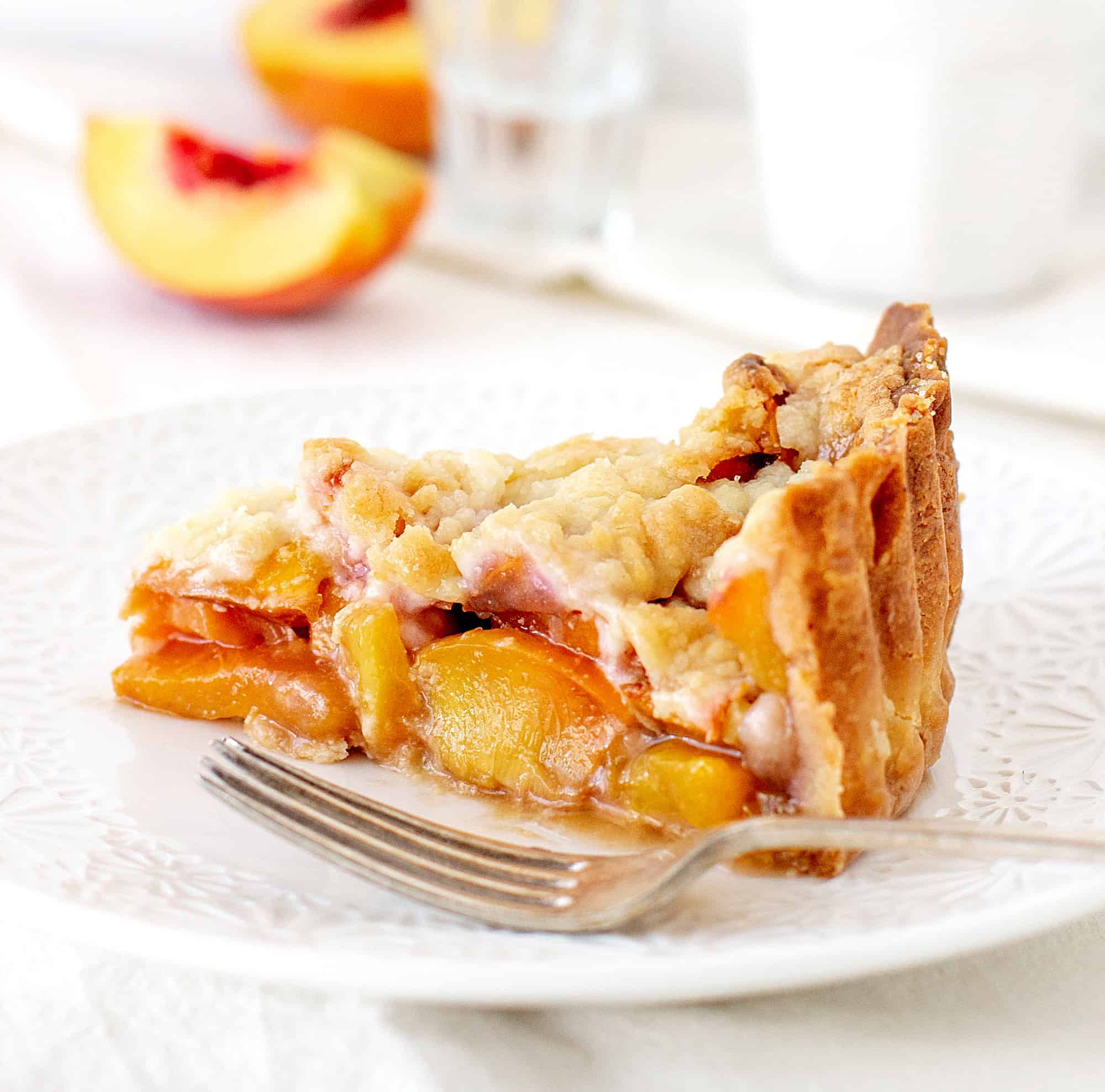 Slice of peach pie on white plate, silver fork, white background, peach wedges