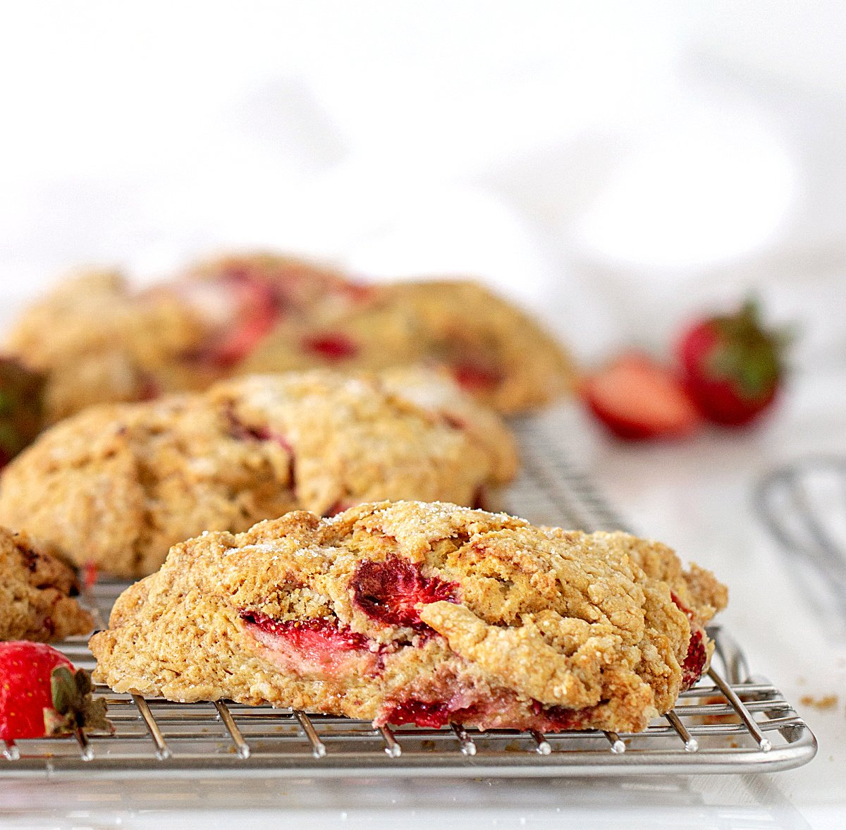 Strawberry scones on silver wire rack, white background