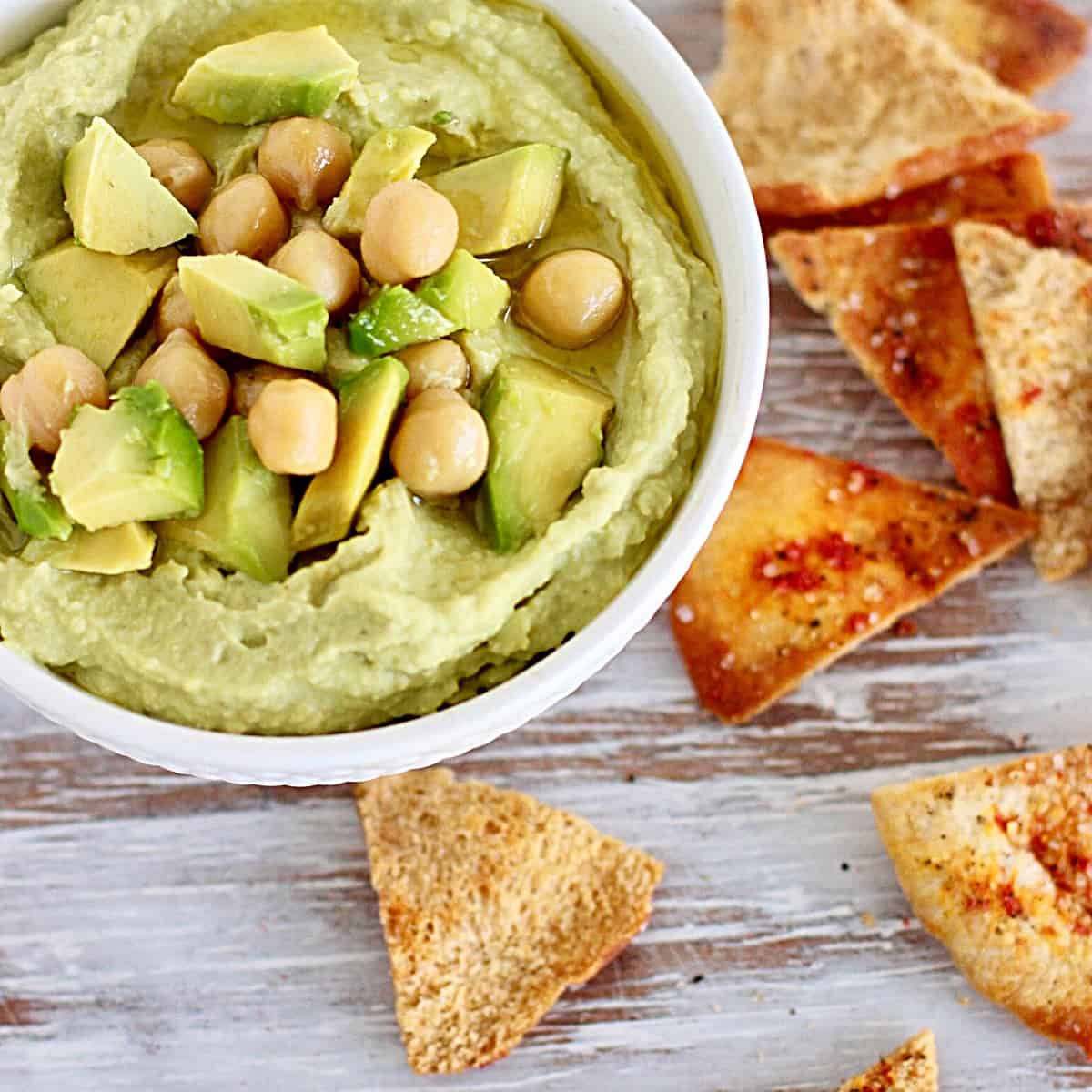 White bowl with green dip, chickpeas and pita chips; on white wooden table