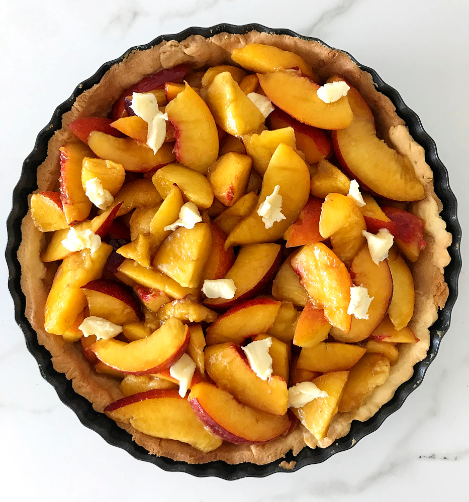 Peach filling in meatl pie pan on white marble surface