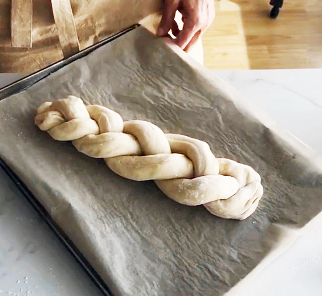 Raw braid of dough on parchment lined pan