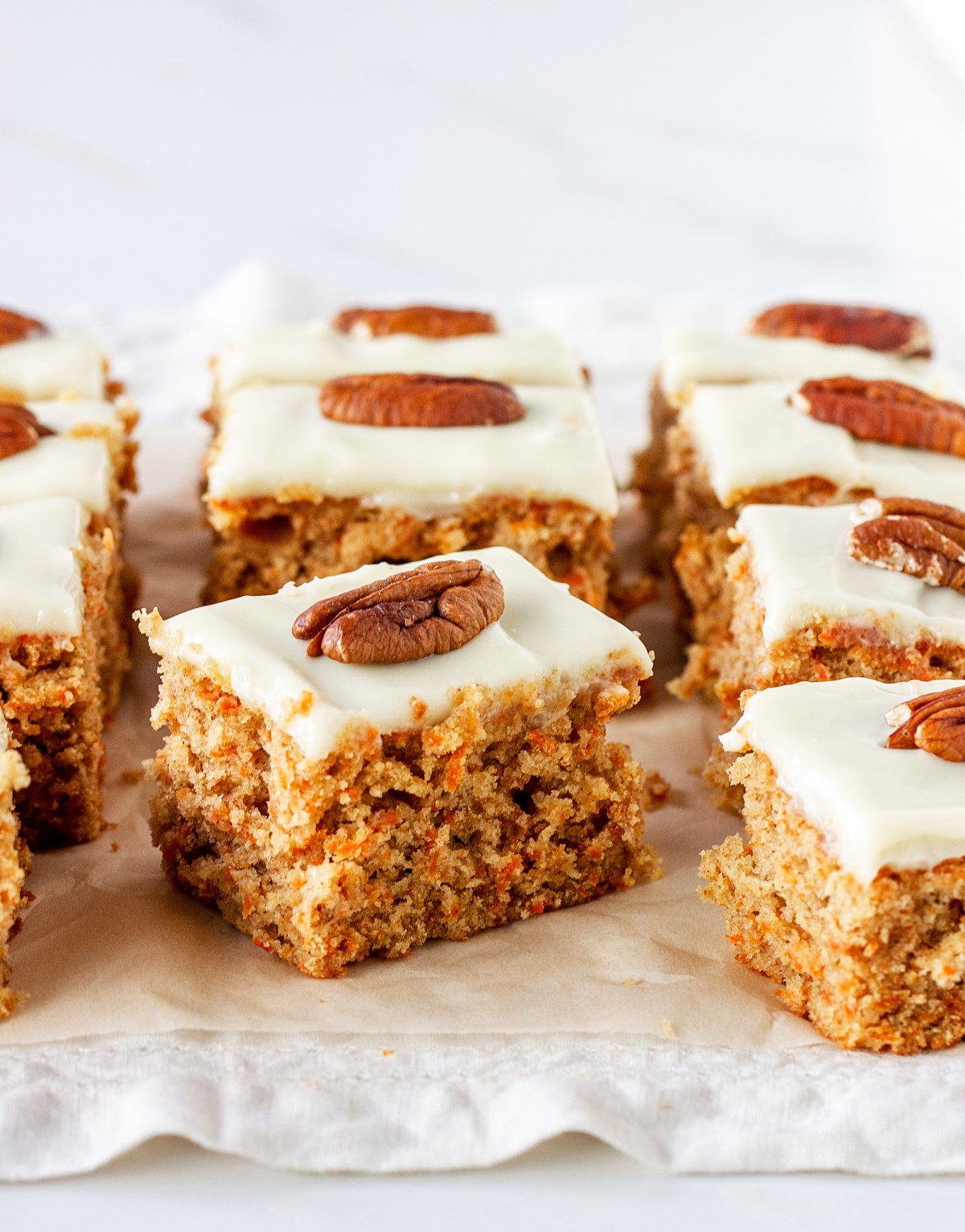 Squares of carrot cake with frosting and pecan, on white paper