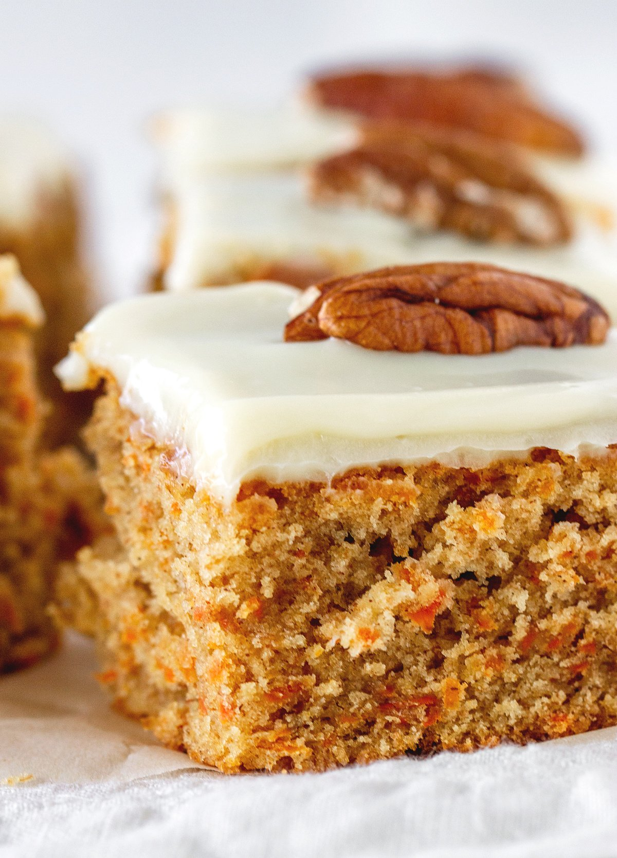 Close-up of frosted carrot cake square topped with whole pecan