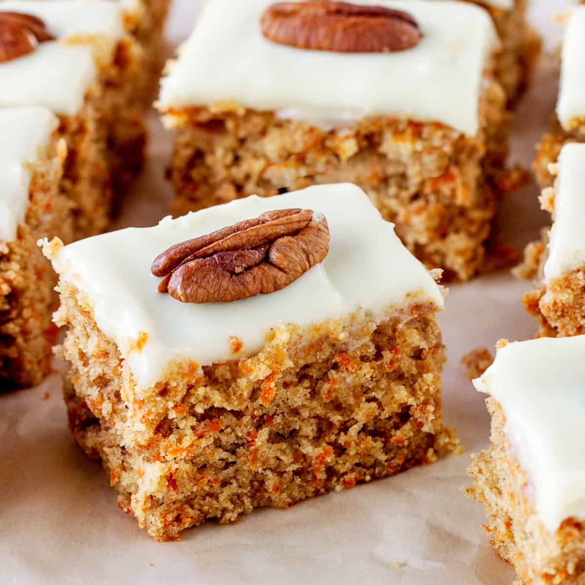 Top view of carrot cake portions, frosted with single pecan as decoration