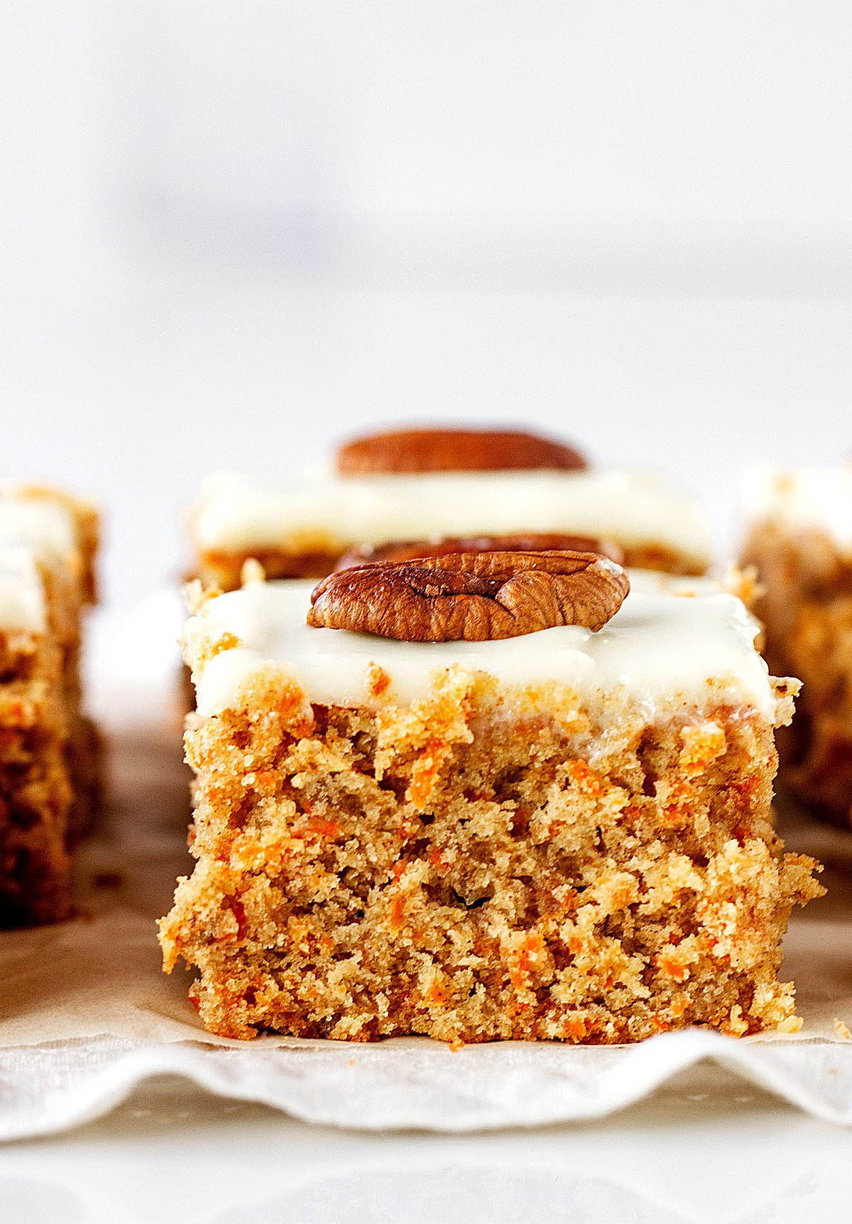 Close-up of square of frosted carrot cake with a pecan piece on a white linen