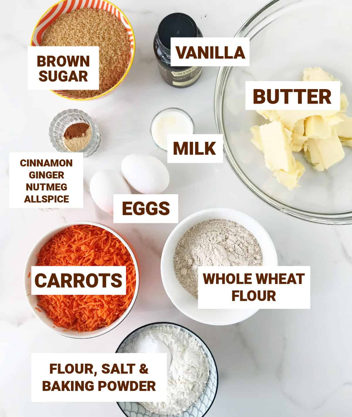 Carrot cake ingredients in small bowls on white surface, including brown sugar, vanilla, grated carrots and spices