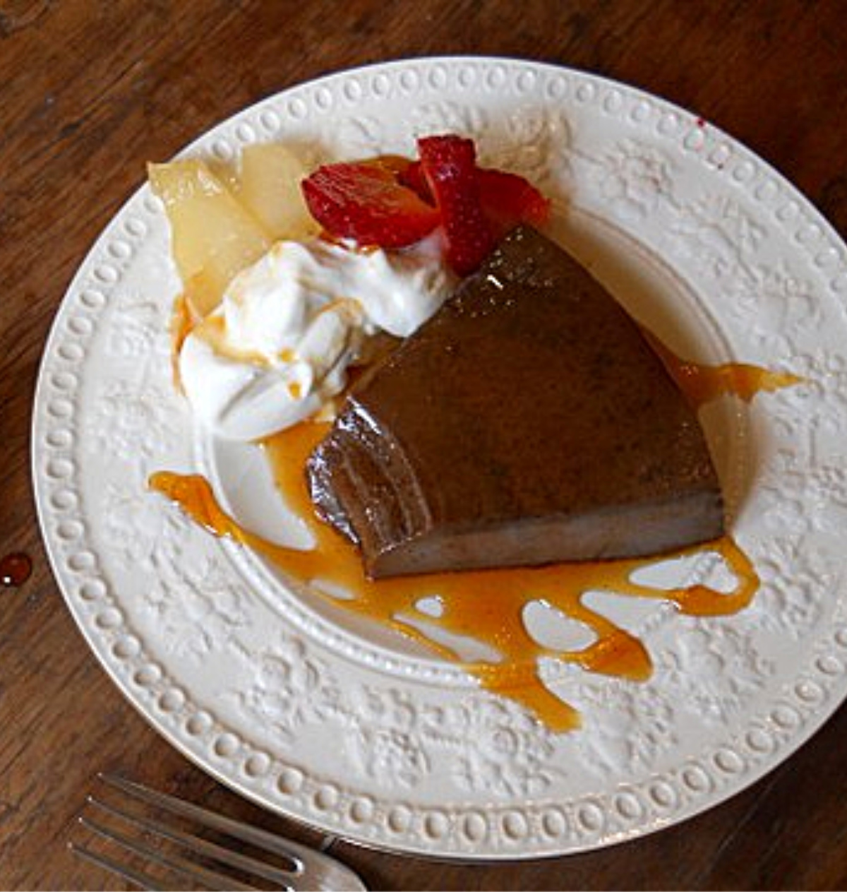 Serving of chocolate flan on white plate, wooden table
