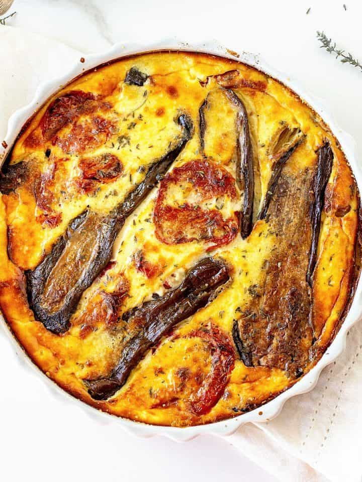 Round dish with baked quiche on white surface